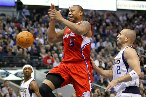 Los Angeles Clippers forward Caron Butler (C) looses the ball as he drives the lane on Dallas Mavericks guard Jason Kidd (R) while guard Jas