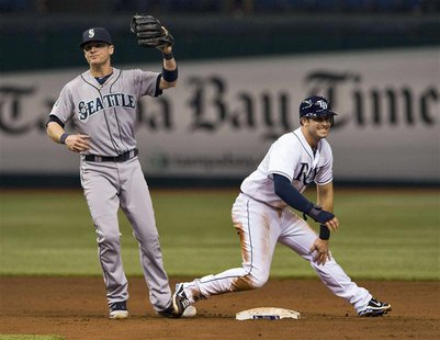 Tampa Bay Rays' Evan Longoria (R) holds his left knee and grimaces after he was tagged out by Seattle Mariners shortstop Brendan Ryan (L) tr