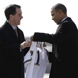 Wisconsin Governor Scott Walker (L) presents U.S. President Barack Obama with a Milwaukee Brewers jersey upon his arrival in Milwaukee, Wisc