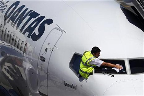 A ground crew member cleans the windshield of a Qantas passenger plane at Adelaide airport in this February 13, 2012 file photo. REUTERS/Tim