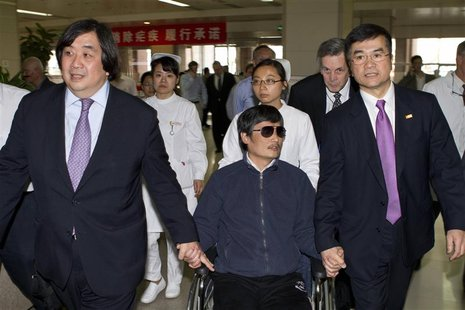 A handout photo from the U.S. Embassy Beijing Press office shows blind activist Chen Guangcheng (C) sitting in a wheelchair as he is accompa