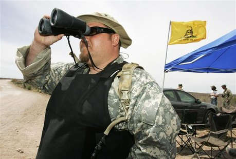 "Minuteman Project volunteer Jason Todd ""JT"" Ready uses binoculars to scan for potential illegal immigrants while along the US/Mexico border"