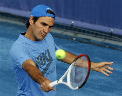 Roger Federer of Switzerland returns the ball during a training session at the Madrid Open tennis tournament in Madrid May 4, 2012. The trad