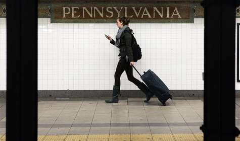 A woman wheels luggage along the subway platform at the 34th Street Penn Station stop in New York November 23, 2011. REUTERS/Shannon Staplet