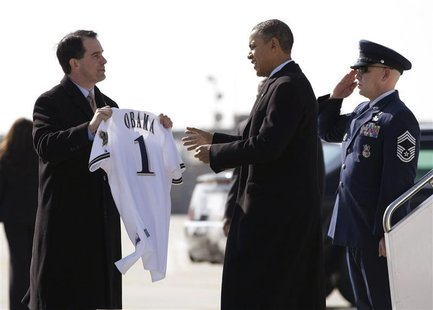 Wisconsin Governor Scott Walker presents U.S. President Barack Obama with a Milwaukee Brewers jersey upon his arrival in Milwaukee, Wisconsi
