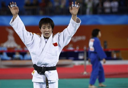 Japan's Tomoko Fukumi walks away as China's Wu Shugen celebrates after their women's -48kg judo competition at the 16th Asian Games in Guang