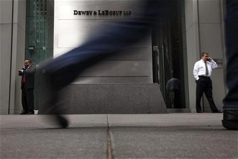 Pedestrians walk past a sign outside of the building housing the law firm Dewey & LeBoeuf LLP in New York, May 8, 2012. REUTERS/Lucas Jackso