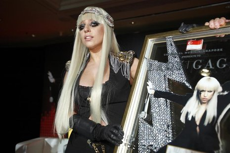 U.S. singer Lady GaGa poses with a plaque presented to her by Universal Music Group during a media event for the launch of Singtel's AMPed m