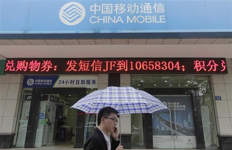A man walks past a branch of China Mobile as he talks on his mobile phone on a rainy day in Wuhan, Hubei province April 20, 2012. REUTERS/St