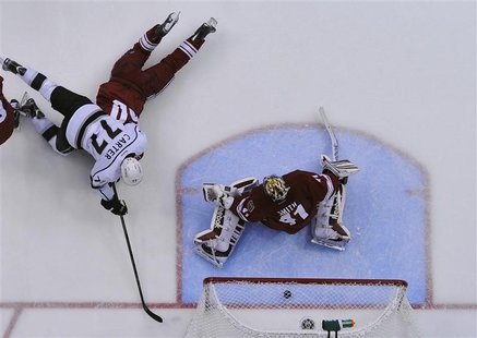 Los Angeles Kings' Jeff Carter (77) scores on Phoenix Coyotes' goalie Mike Smith (41) while falling on top of Coyotes' Antoine Vermette duri