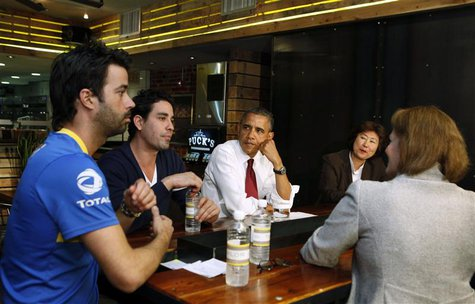 U.S. President Barack Obama talks with small business owners to discuss income tax credits during a roundtable discussion at Taylor Gourmet