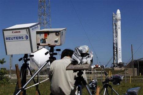 News photographers work on their remote cameras as the SpaceX Falcon 9 test rocket is being prepared for a second launch attempt from Space