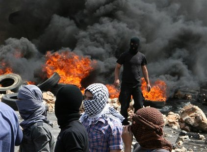 Lebanese Sunni Muslim men, with faces covered, stand, after they burnt tyres to block a road to protest the killing of Sheikh Ahmed Abdul Wa