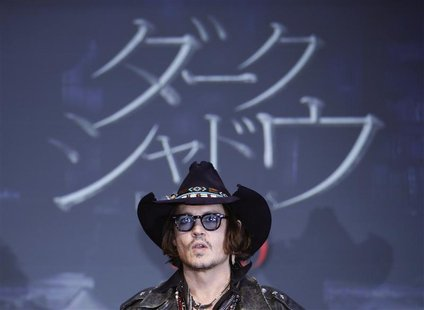Actor Johnny Depp poses in front of a screen showing the name of the film in Japanese during a photo call at a news conference for their fil