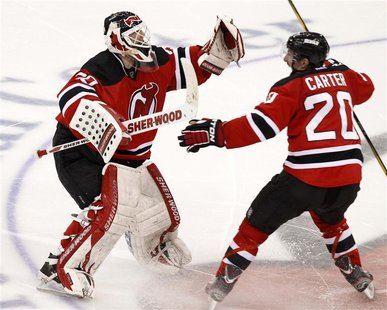 New Jersey Devils goalie Martin Brodeur (L) celebrates with teammate Ryan Carter after the Devils defeated the New York Rangers in Game 6 of