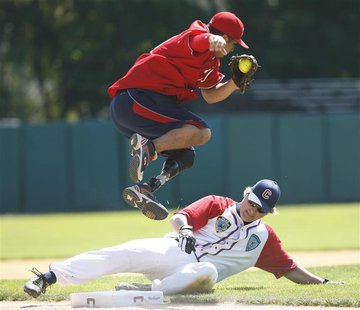 Wounded Warrior Amputee Softball Team third baseman Saul Bosquez (top) leaps out of the way of an unidentified base runner during their game