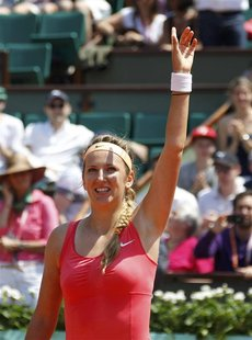 Victoria Azarenka of Belarus waves after winning her match against Alberta Brianti of Italy during the French Open tennis tournament at the
