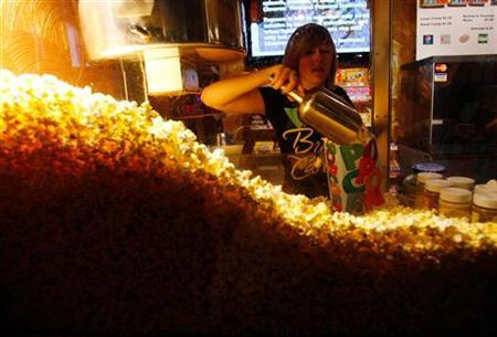 Cailynn Williams, 17, fills a bag of popcorn for a customer at the New Strand Theater in West Liberty, Iowa July 8, 2011.   Credit: Reuters/Jessica Rinaldi