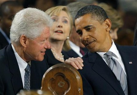 U.S. President Barack Obama (R) talks with former U.S. President Bill Clinton (L) and his wife, Secretary of State, Hillary Clinton (C) duri