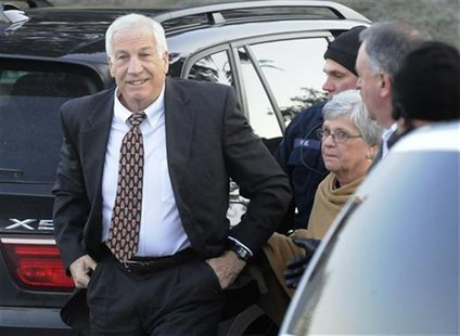 Former Penn State assistant football coach Jerry Sandusky (L) gets out of a car with his wife Dottie (2nd R) as he arrives for a preliminary