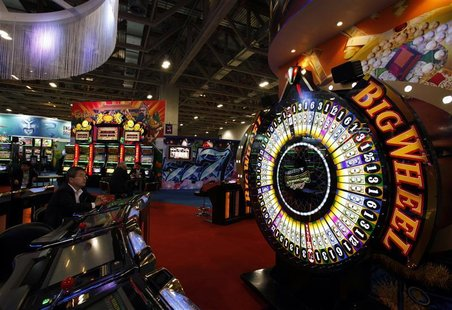 A visitor sits in front of a gaming machine at Gaming Expo Asia in Macau May 22, 2012. REUTERS/Bobby Yip