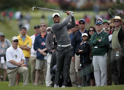 Tiger Woods of the U.S. hits a second shot out of the crowd on the 10th hole during the third round of the Memorial Tournament at Muirfield