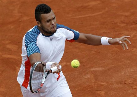 Jo-Wilfried Tsonga of France returns the ball to Stanislas Wawrinka of Switzerland during the French Open tennis tournament at the Roland Ga