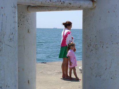 Visitors to the pier at Holland State Park watch the SS Keewatin sail by on Monday, June 4.