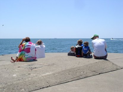 Visitors to the pier at Holland State Park watch the SS Keewatin sail past on Monday, June 4.
