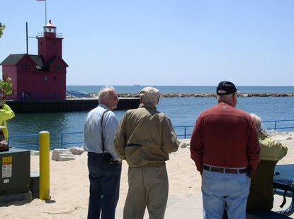 Visitors to Holland State Park watch the SS Keewatin sail on Lake Michigan past Holland Harbor on Monday, June 4.