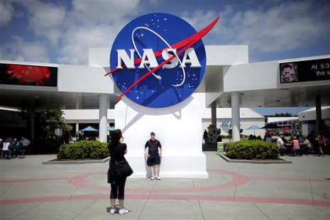 Tourists take pictures of a NASA sign at the Kennedy Space Center visitors complex in Cape Canaveral, Florida April 14, 2010. President Bara