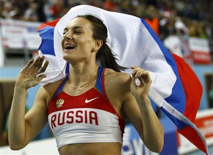 Gold medalist Yelena Isinbayeva of Russia holds her national flag after the women's pole vault final during the world indoor athletics champ