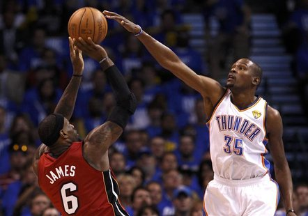 Miami Heat's LeBron James (L) is guarded by Oklahoma City Thunder's Kevin Durant during the first quarter in Game 1 of the NBA basketball fi