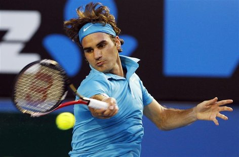 Roger Federer of Switzerland hits a return against France's Jo-Wilfried Tsonga during their semi-final match at the Australian Open tennis t