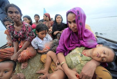 Rohingya refugees from Myanmar sit on a boat as they try to get into Bangladesh in Teknaf June 13, 2012. REUTERS/Andrew Biraj