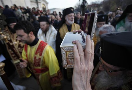 "A Bulgarian East-Orthodox priest holds up a box containing bones, believed to be the relics of John the Baptist, in front golden-domed ""Alex"