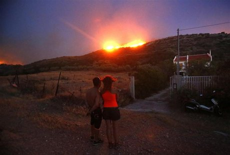 Locals look at a forest fire approaching their house at Thymari coastal village, 40 km (25 miles) southeast of Athens, June 16, 2012. REUTER