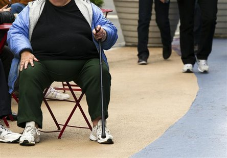 An overweight woman sits on a chair in Times Square in New York, May 8, 2012. America's obesity epidemic is so deeply rooted that it will ta