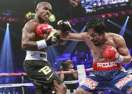 Timothy Bradley Jr. (L) of the U.S. exchanges blows with WBO welterweight champion Manny Pacquiao of the Philippines during their title figh