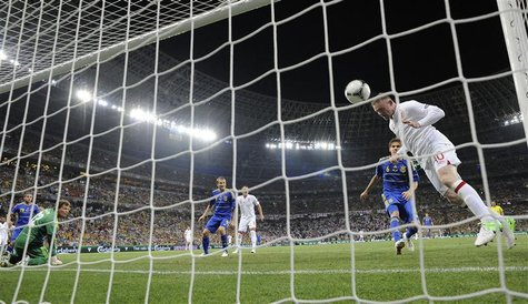 England's Wayne Rooney (R) shoots to score a goal as Ukraine's goalkeeper Andriy Pyatov (L) watches during their Group D Euro 2012 soccer ma