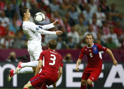 Portugal's Cristiano Ronaldo controls the ball in front of Czech Republic's Michal Kadlec (C) and David Limbersky (R) during their Euro 2012