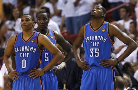 Oklahoma City Thunder's Russell Westbrook (0), Kendrick Perkins (5) and Kevin Durant pause during a time out against the Miami Heat during G