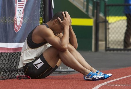 Bryan Clay sits against a fence after failing to clear the last hurdle in the decathlon 110m hurdles at the U.S. Olympic athletics trials in