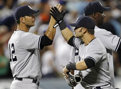 New York Yankees' Eric Chavez (L) and teammate Nick Swisher celebrate their win against the New York Mets in their MLB Interleague baseball