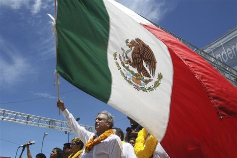 Andres Manuel Lopez Obrador, presidential candidate for the Party of the Democratic Revolution (PRD), holds Mexico's national flag during a