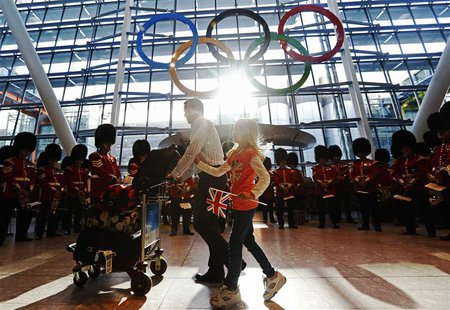 Travellers pass the Olympic Rings during an unveiling ceremony in the Terminal Five arrivals hall at Heathrow Airport, in preparation for th