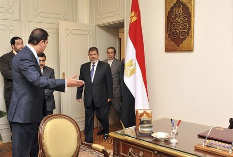 Muslim Brotherhood's President-elect Mohamed Mursi (C) arrives to his office at the Presidency, in Cairo June 25, 2012. REUTERS/Middle East