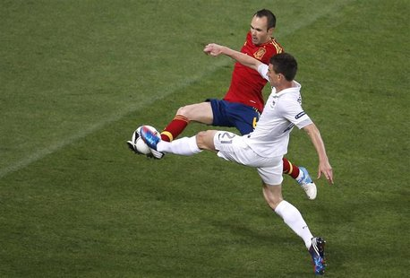 Spain's Andres Iniesta (L) fights for the ball with France's Laurent Koscielny during their Euro 2012 quarter-final soccer match at the Donb