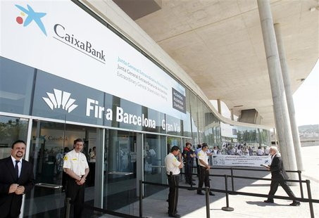 People protest at the entrance of Caixabank's extraordinary general shareholders meeting, where the approval of the decision for the merger