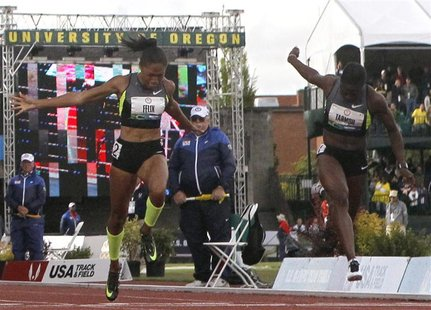 Allyson Felix (L) and Jeneba Tarmoh cross the finish line during the women's 100 meters final at the U.S. Olympic athletics trials in Eugene